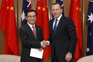 Australian Prime Minister Tony Abbott shakes hands with China's Minister of Commerce Gao Hucheng during an official meeting in Canberra
